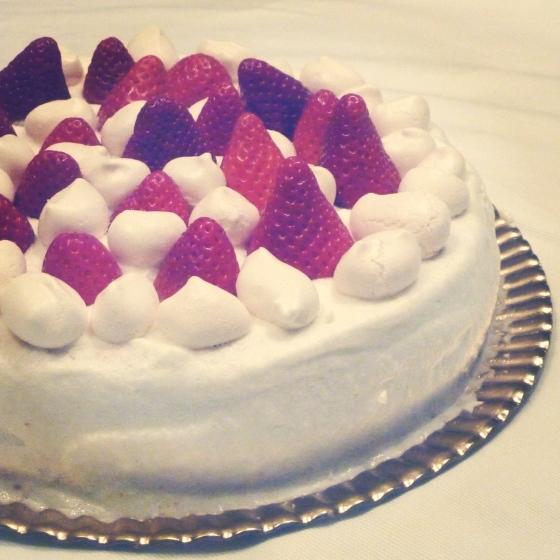 bolo fofo com recheio de ovos moles e cobertura de natas, morangos e suspiros